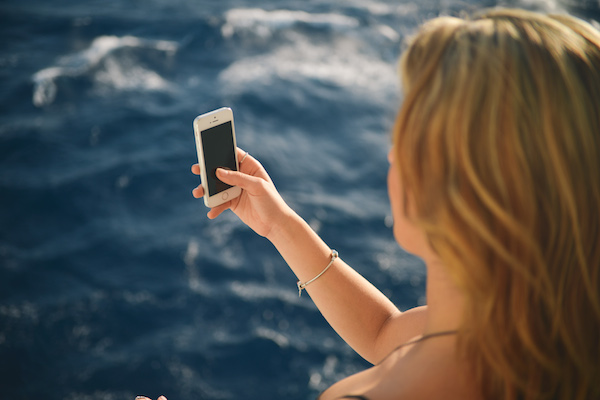 Woman Using Smartphone  With Beautiful Blue Ocean