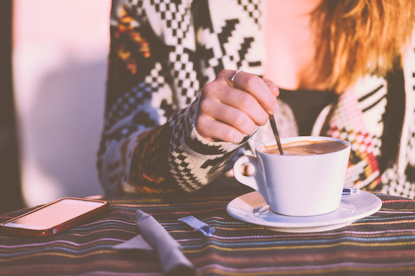 Girl-Stirring-Early-Morning-Coffee-In-A-Cafe How One Couple Drastically Changed Their Life by Blogging