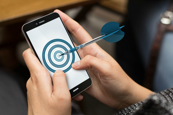 mobile advertising, marketing or goals concept: girl using a digital generated phone with target on the screen. All screen graphics are made up.